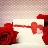 Hjärtahälsningkort med röda rosor Arkivbild