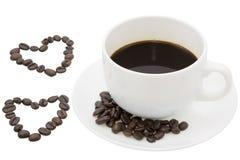 Hjärtakaffebönor med svart kaffe på vit bakgrund Arkivfoto