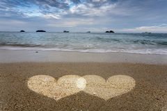 Hjärtaljus i sand på havstranden Arkivfoto