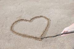 hjärtan dras på sanden på stranden med en pinne som du kan Royaltyfria Foton