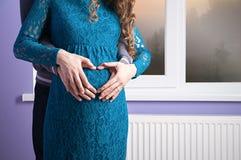 Hjärtan på en gravid kvinnas mage royaltyfria foton