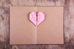 Hjärtaorigami och bok med tomma sidor Rosa hjärta som göras av papper och dagboken Arkivbilder