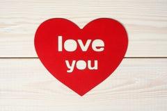 Hjärtasnitt från rött papper med inskriftförälskelse dig Arkivbild