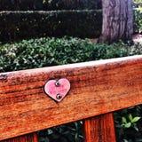 Hjärtasymbol på en bänk arkivfoton