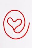 Hjärtasymbol som göras av tråd Arkivbild