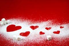 Hjärtor av socker på röd bakgrund Royaltyfri Foto