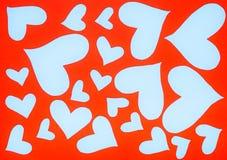 Hjärtor formar rött pappers- klipp på blå bakgrund arkivfoto