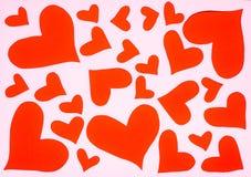 Hjärtor formar rosa pappers- klipp på röd bakgrund arkivbilder