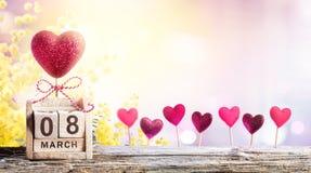 8 hjärtor med mimosan och kalendern för kvinnadag Arkivbilder