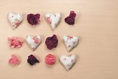 Hjärtor och vissnade rosor på pastellfärgad träbakgrund Royaltyfria Foton
