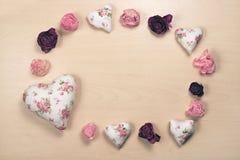 Hjärtor och vissnade rosor på pastellfärgad träbakgrund Royaltyfri Bild