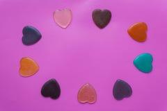 Hjärtor på rosa färg-lilor bakgrund valentin för dagvykort s Arkivfoton