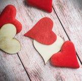 Hjärtor som göras av filt och trä på tabellen Arkivfoto