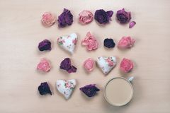 Hjärtor, vissnade blommor och kopp kaffe på pastellfärgad träbakgrund Arkivbild