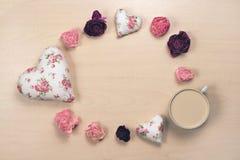 Hjärtor, vissnade blommor och kopp kaffe på pastellfärgad träbakgrund Royaltyfri Bild