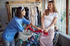 Hj?lpande kunder f?r s?ljarekvinna till att k?pa den nya cykeln i lager arkivfoton