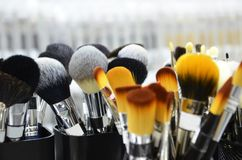 Hj?lpmedel av produkter f?r borste f?r kvinnask?nhetmode kosmetiska f?r ansiktsbehandling Olika makeupborstar p? ljus bakgrund me arkivfoton