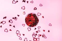 Hj?rta-formade konfettier p? rosa bakgrund arkivbild