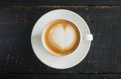 Hj?rta formar fradga mj?lkar Lattekonst i kopp f?r vitt kaffe p? den svarta tr?tabellen royaltyfri foto
