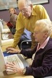 hjälpande manpensionär för dator som använder kvinnan Arkivbild