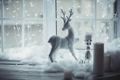 Hjortarna figurerar anseende på fönstret på bakgrunden av juldekoren Vänta ett mirakel Arkivbilder