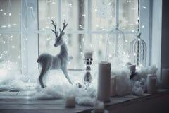Hjortarna figurerar anseende på fönstret på bakgrunden av juldekoren Vänta ett mirakel Royaltyfri Foto