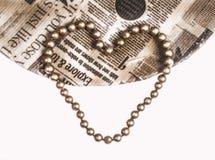 Hjärta formad guld- pärla på tappningtidningen Arkivbild
