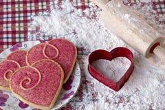 Hjärta formad kakor och skärare Arkivbilder