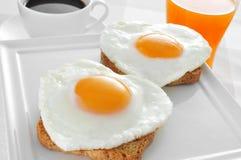 Hjärta-formade stekte ägg, bröd och orange fruktsaft Arkivfoto