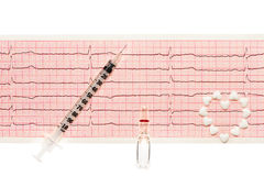 Hjärta som göras av vita hjärtaformminnestavlor, den genomskinliga vita glass ampullen med en drog och den plast- injektionssprut Royaltyfri Foto