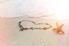 Hjärtaform som tecknas på sanden Förälskelse bröllopsresa, bakgrund för sommarferie Effekt för kamera för ljusläckafilm Royaltyfri Fotografi