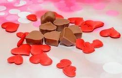 Hjärtaformchoklad med röda hjärtor, valentindagsötsaker, rosa bokehbakgrund Royaltyfri Foto