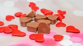 Hjärtaformchoklad med röda hjärtor, valentindagsötsaker, rosa bokehbakgrund Arkivfoto
