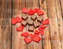 Hjärtaformchoklad med röda hjärtor, valentindagsötsaker, wood bakgrund Arkivbild