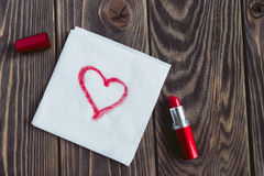 Hjärtatecknet på en servett målade vid lipstik Arkivbilder