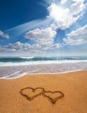 Hjärtor som dras på sanden av en strand Arkivfoto