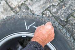 Hjuländring och märker gummihjulen med färgpennan Arkivfoto