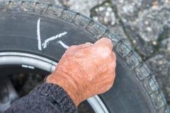 Hjuländring och märker gummihjulen med färgpennan Arkivbild