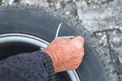 Hjuländring och märker gummihjulen med färgpennan Royaltyfria Bilder