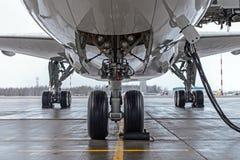 Hjul för landningkugghjul som och flygplanparkeras på flygplatsen, med grundläggande strömförsörjning royaltyfria foton