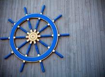 Hjul för roder för gamla tappningblått träpå väggen royaltyfri fotografi