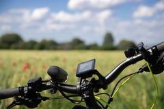 Hjul från cykeln med navigeringapparater på bakgrunden av ett fält för vårråg med röda vallmo I avståndet finns det arkivbilder