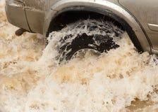 Hjulbilar i grovt vatten Fotografering för Bildbyråer