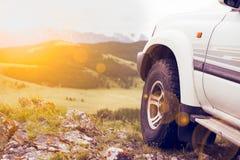 Hjulet av en SUV på en klippa i bergen Royaltyfri Bild