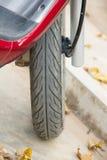 Hjulet av ett rött som vara nedstämd på marmor som ser tegelplattor Royaltyfri Bild