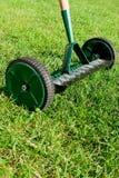 Hjulet krattar på gräs. arkivfoto