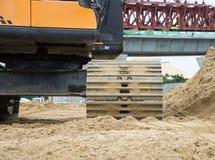 Hjulladdargrävskopan med backhoen som lastar av sand på eath, fungerar Arkivfoto