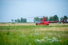 Hélicoptère Robinson R44 dans un pré près d'airoport de Nida Photographie stock libre de droits