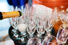 Häll champagne in i exponeringsglas på brölloppartiet Arkivfoton