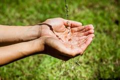 Häll rent vatten för att räcka brutet vatten i hand Arkivfoton